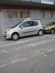 Coche de autoescuela estacionado sobre un paso de peatones