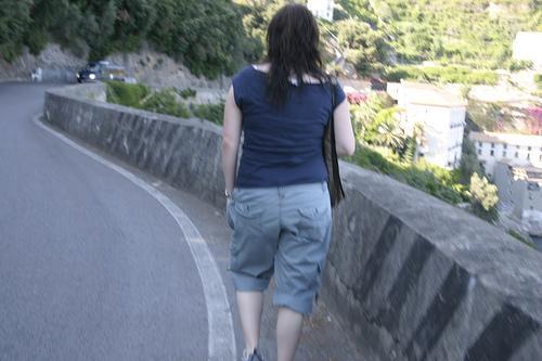Peatón caminando por el lado derecho de una carretera, de espaldas al tráfico