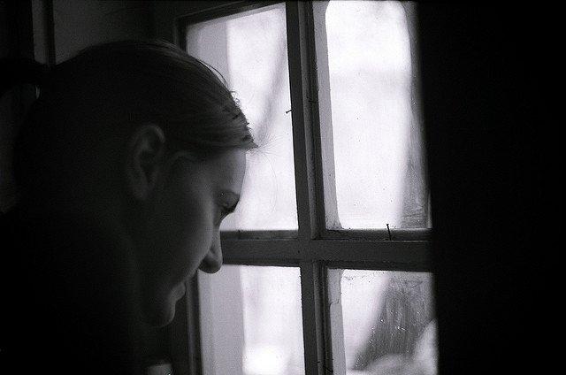 Mirando por la ventana con el teléfono en la mano, esperando