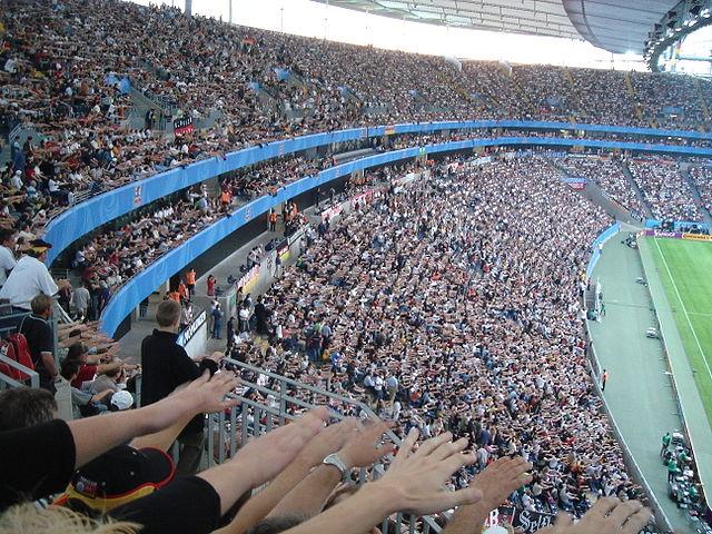 La ola: los espectadores, sin moverse, transmiten una perturbación en el movimiento de sus brazos
