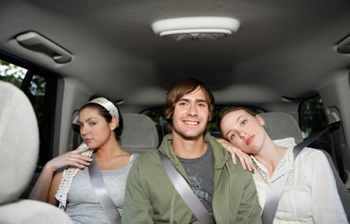 Young man sitting with two women on back seat (portrait)
