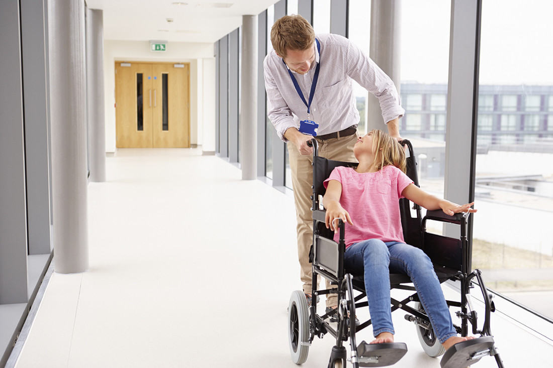 Doctor Pushing Girl In Wheelchair Along Corridor