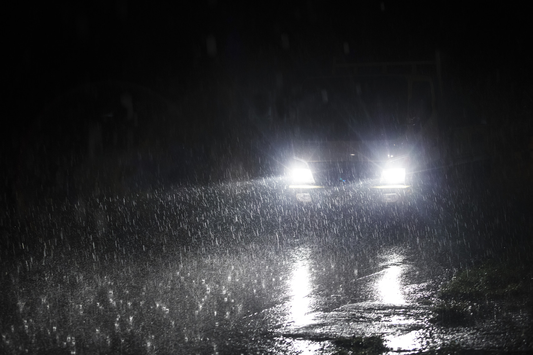 Yellow headlight and road in the dark while heavy raining.
