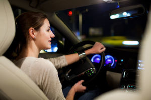 Driving a car at night - pretty, young woman driving her modern