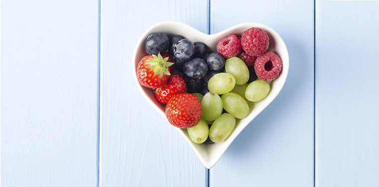 Overhead shot of a selection of fruits in a heart shaped bowl, on a light blue wood planked surface.