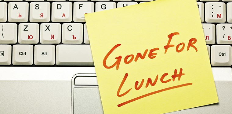Yellow sticky note on a laptop keyboard with 'Gone for Lunch' on it.