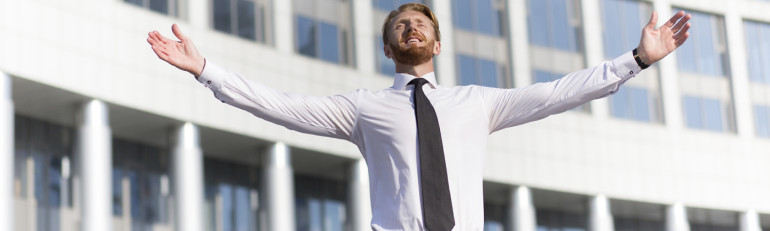Successful businessman celebrating with arms up. Man in white shirt with tie looking at the sky and happy smiling.