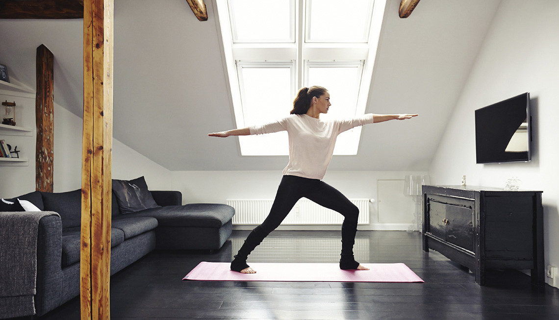 Full length image of attractive young woman exercising on mat in living room. Fit lady doing yoga at home.