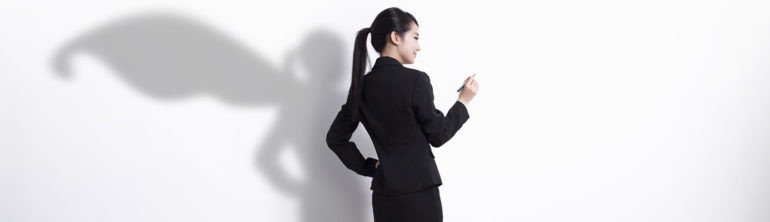 Back view of Superhero business woman writing something on white wall background, great for your design or text, asian
