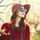 portrait of beautiful young woman with black sunglasses standing near blooming tree