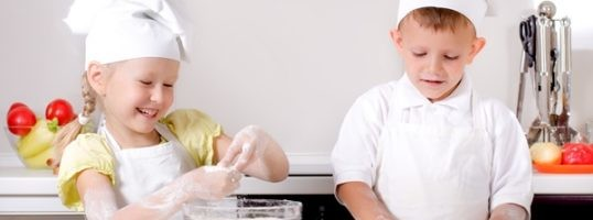 Happy little boy and girl wearing a white chefs uniform and hat cooking in the kitchen standing at the counter making a batch of biscuits and rolling the dough