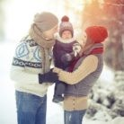 Happy young family portrait on winter surrounded by snow.