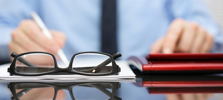 blurred businessman is working in office , focus is on eyeglasses