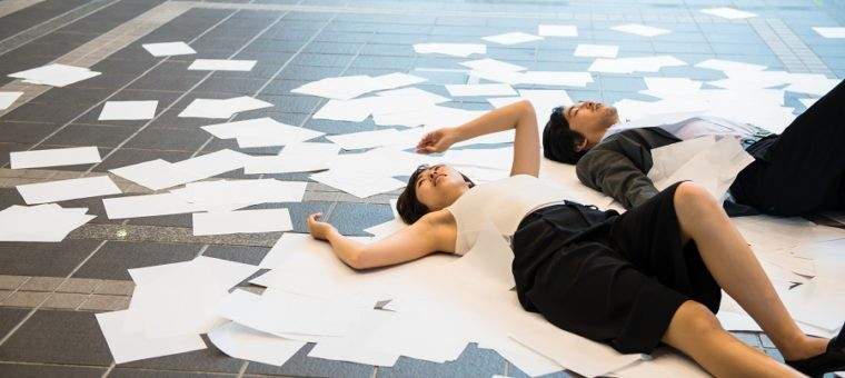 Business man and woman lie down on the floor, paper lay scattered .