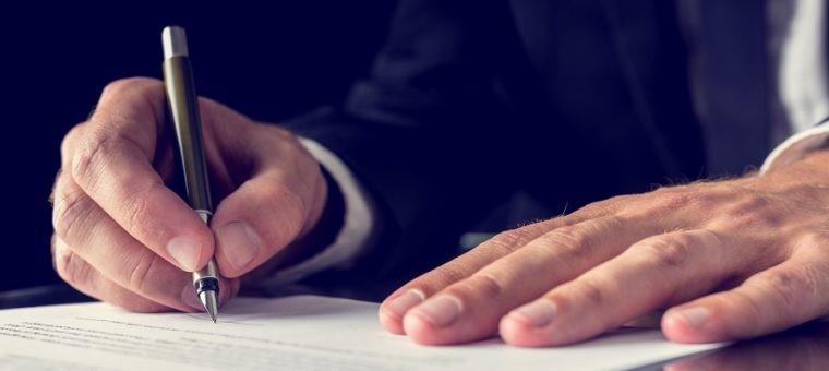 Retro image of lawyer signing important legal document on black desk. Over black background.