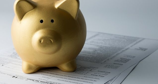Golden piggy bank sitting on income tax form