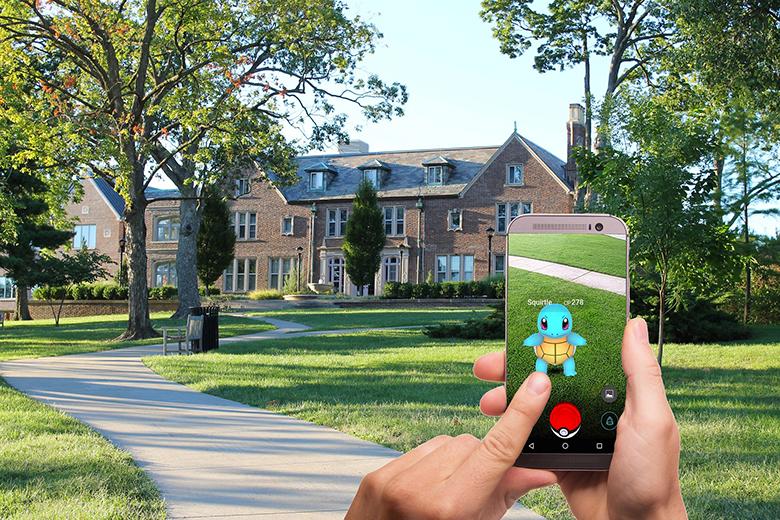 Usuario jugando a Pokémon Go con su móvil en una calle.