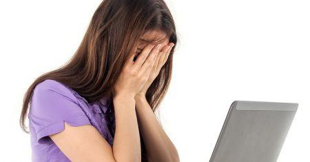 Mujer tapa sus ojos frente a la pantalla del ordenador