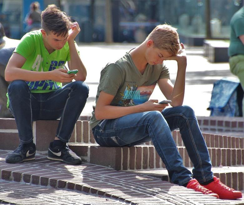 Jóvenes miran su teléfono móvil en la calle