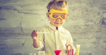 Niña pequeña con bata y gafas de científico