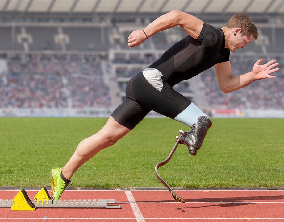 persona con pierna protésica compitiendo en un estadio, de perfil