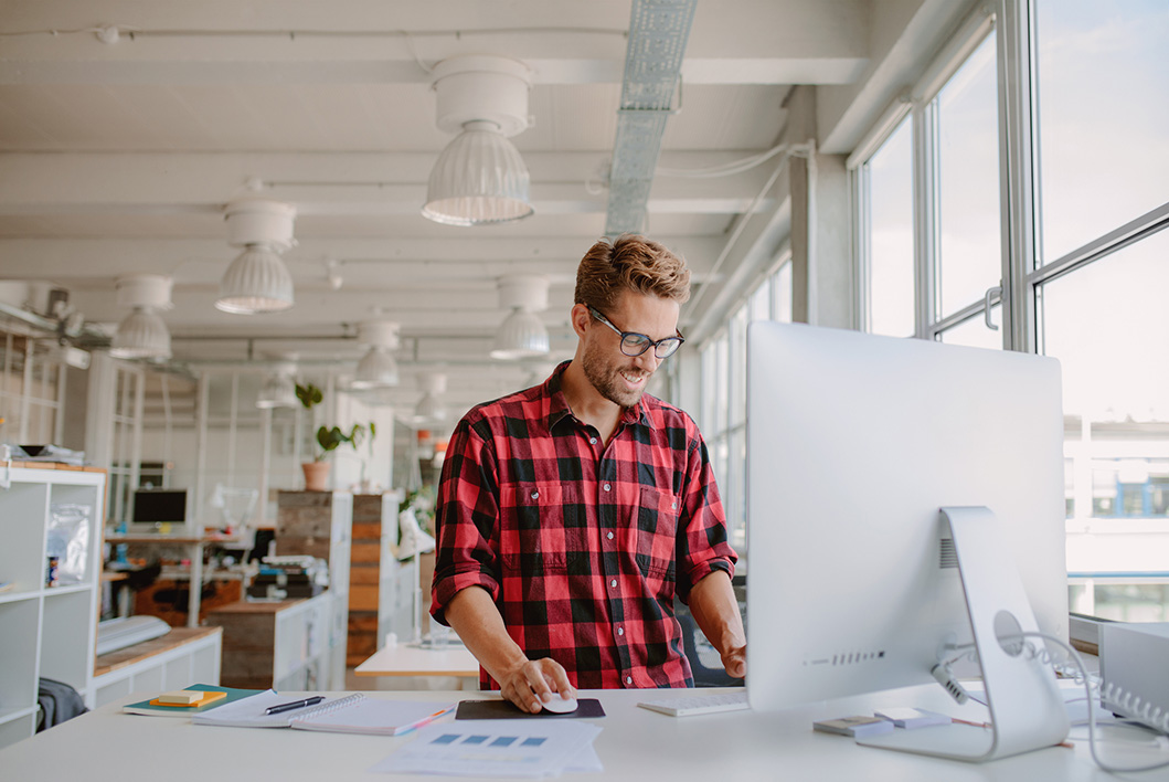 Hombre joven con camisa roja mirando una pantalla de MAC