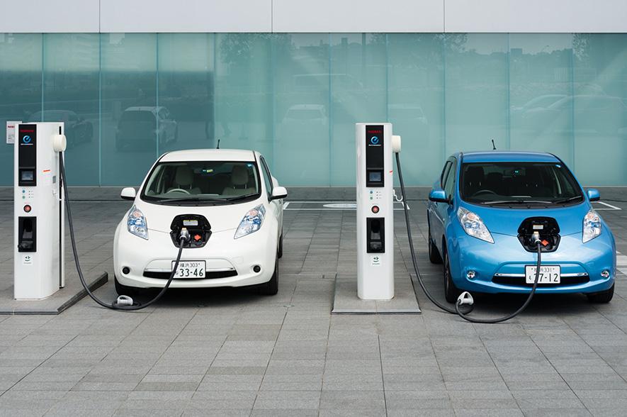 Dos Nissan, blanco y azul, recargando su batería