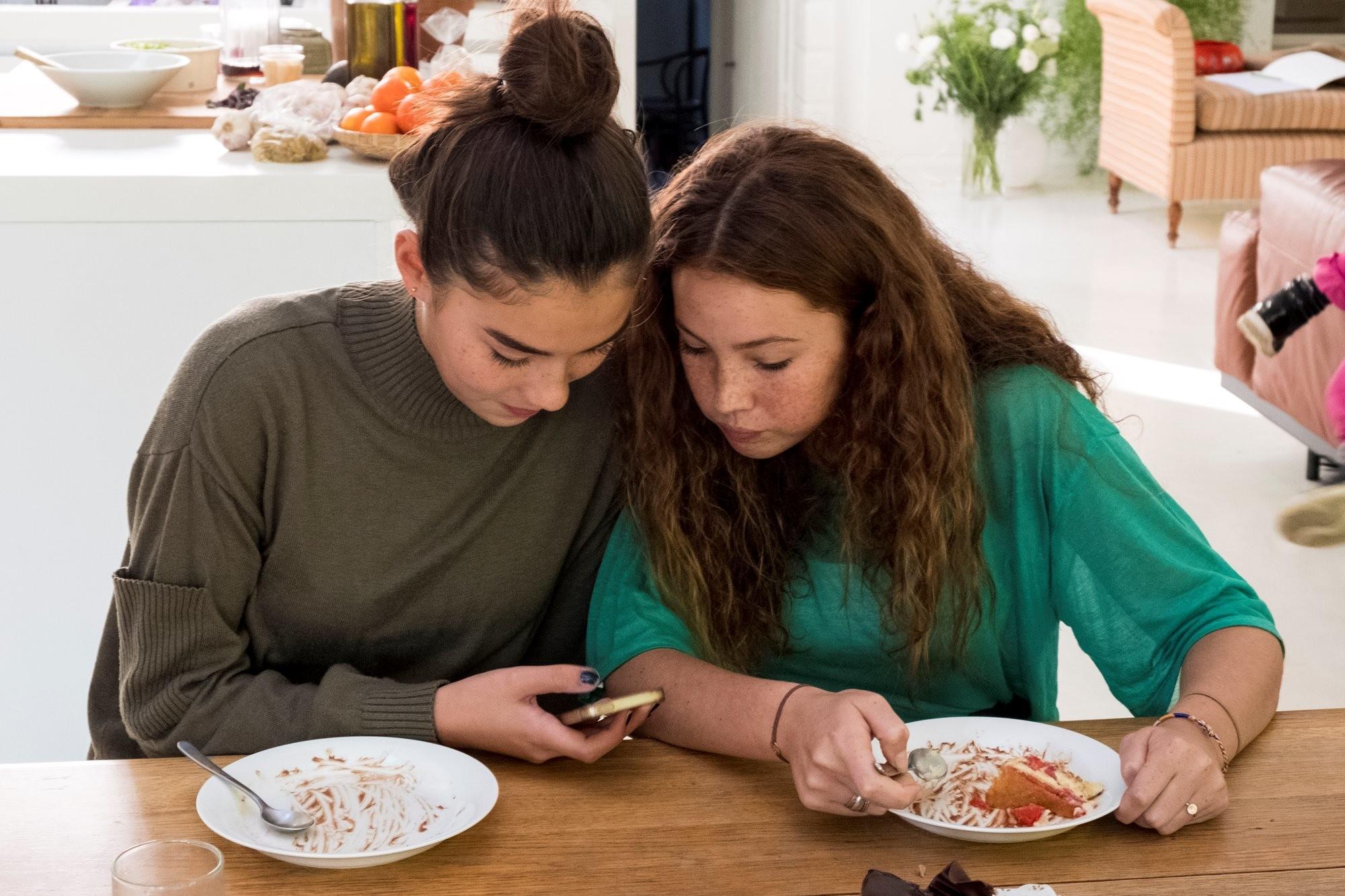 Dos chicas adolescentes miran un teléfono móvil