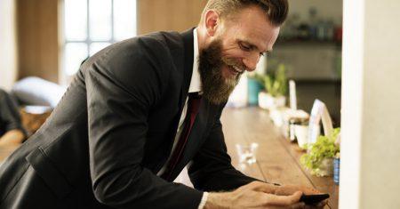 Hombre con barba y móvil en artículo sobre Alarma de Orange
