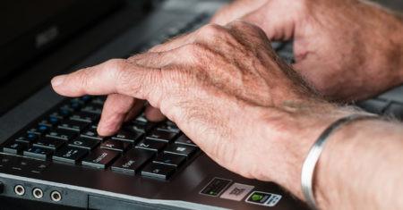 Manos de anciano en teclado. Facebook