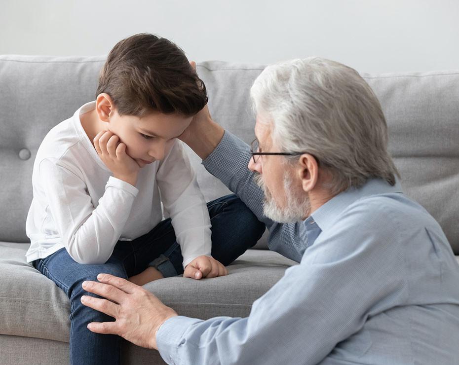 persona mayor consuela a un niño, que se sienta sobre un sofá - artículo psicología de una pandemia