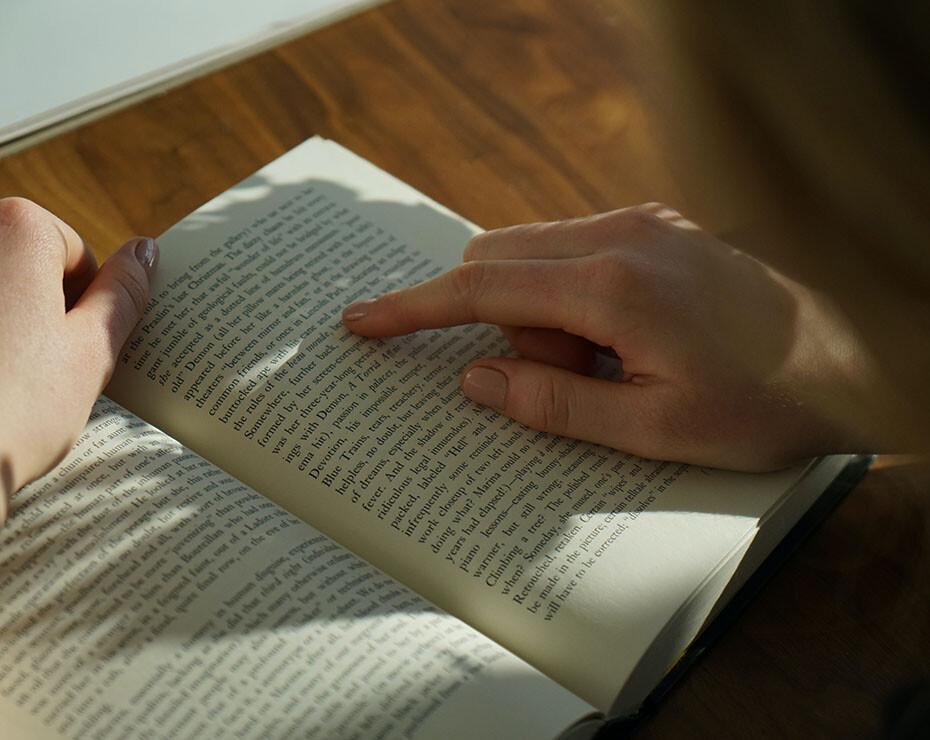 persona leyendo un libro y marcando el texto con el índice