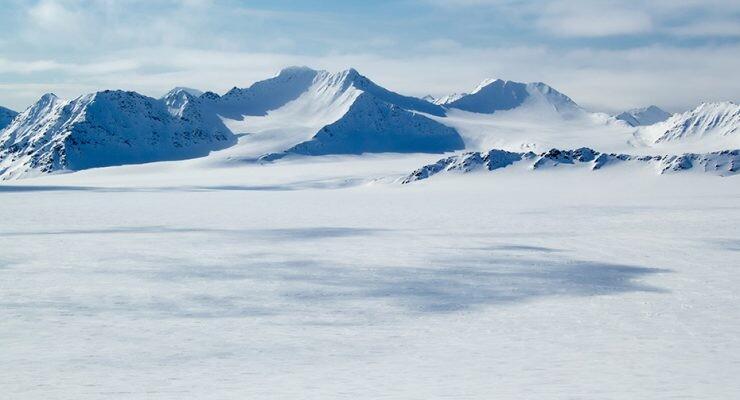 superficie congelada del Ártico con montañas en un día despejado