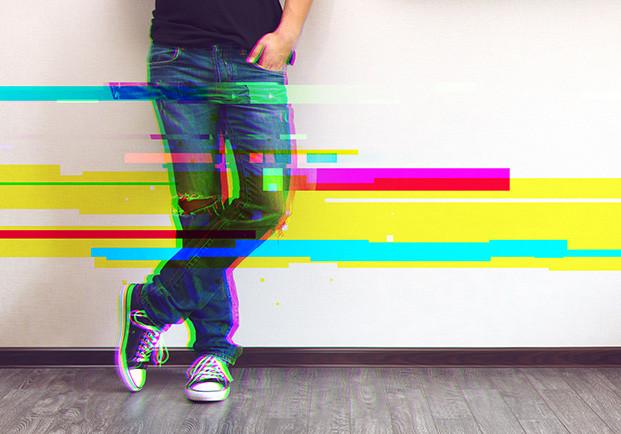 Piernas de un joven apoyado en una pared con trazas de efecto glitch