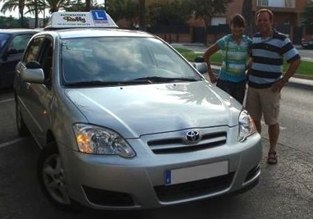 Clàudia Fornos y su padre, junto a un vehículo de la autoescuela