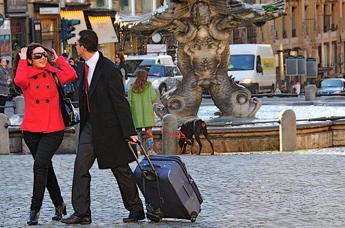 Hombre tirando de una maleta, forzando la espalda