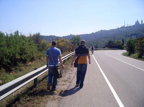 Peatones caminando por el lado izquierdo de la carretera, de cara al tráfico