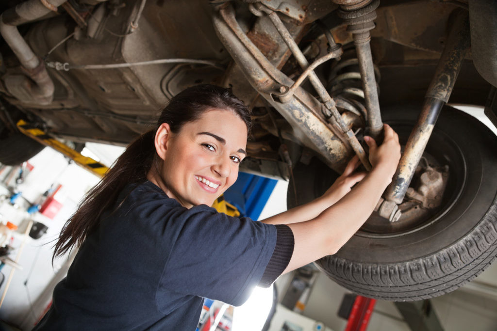 Portrait of smiling young female mechanic inspecting a CV joing on a car in auto repair shop