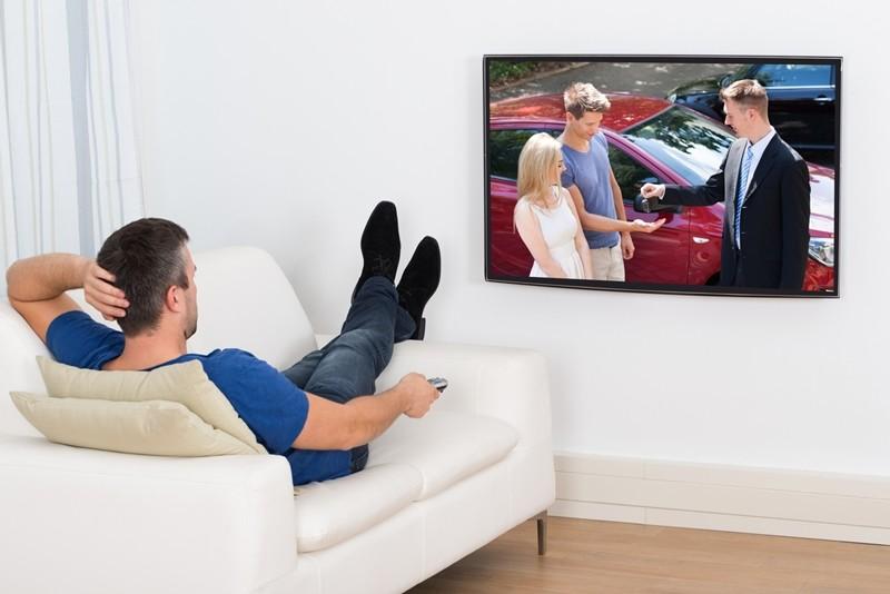 Joven viendo un anuncio de coches