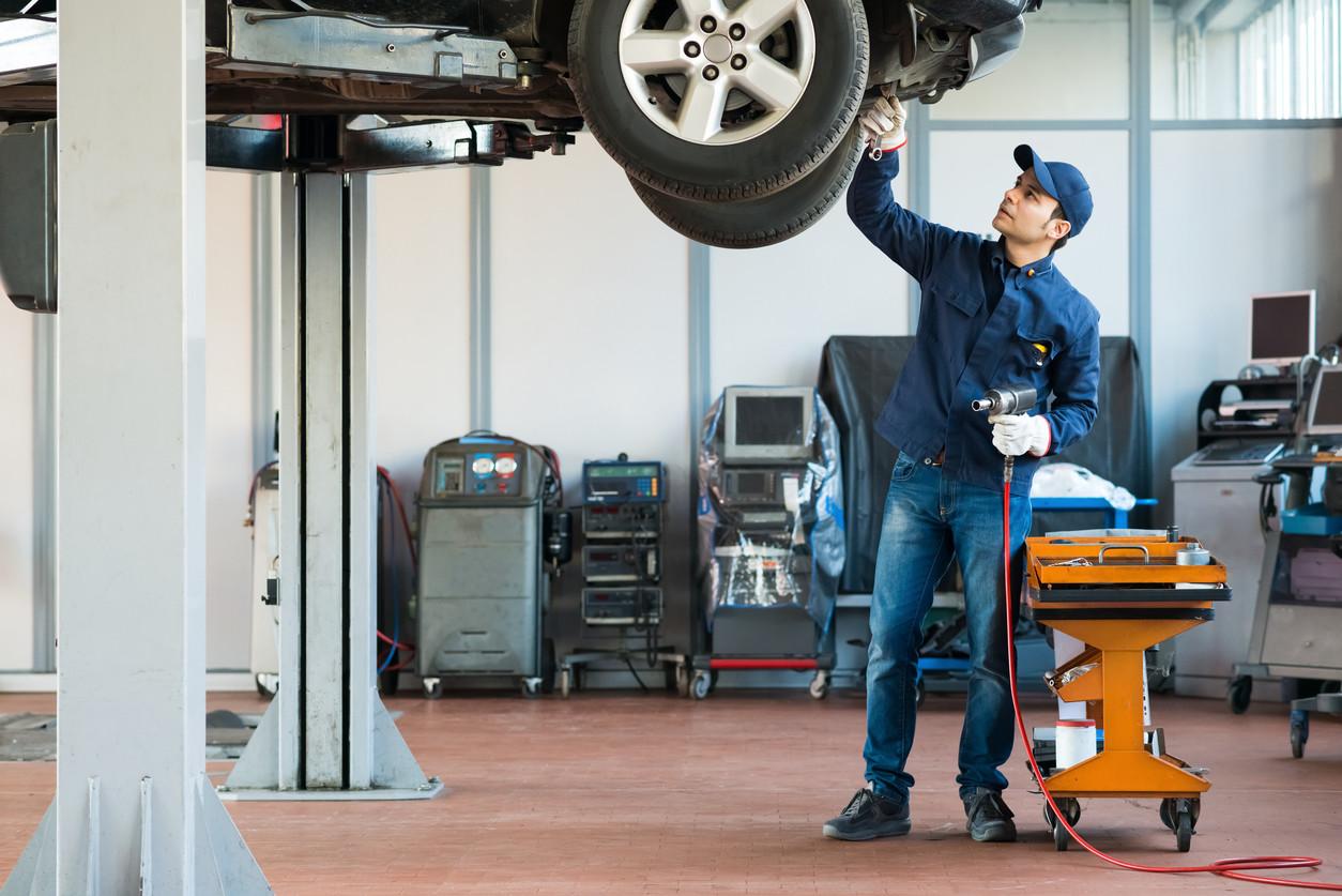 Mecánico en taller con coche