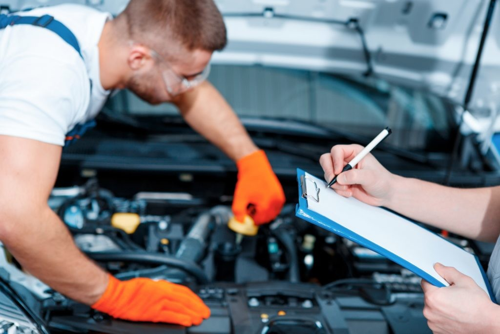 Running diagnostics. Two handsome car mechanics in uniform checking the engine under hood in the car service station and checking in service order