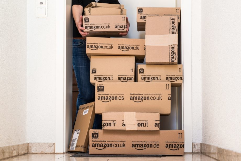 Ostfildern, Germany - May 18, 2014: A woman is horrified by a large stack of parcels by Amazon.com in different sizes waiting in front of the entrance door to her flat on May, 18, 2014 in Ostfildern-Scharnhausen near Stuttgart, Germany. This conceptual photo can serve different purposes: It might demonstrate the domination of Amazon.com in the area of online shopping or the trend in general to shop online for all the different items you need in your personal life.
