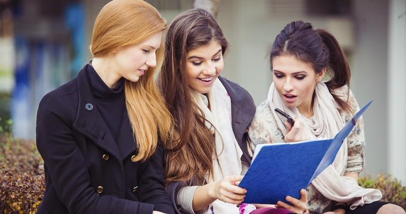Tres mujeres informándose de la evolución de los tres principales índices bursátiles americanos