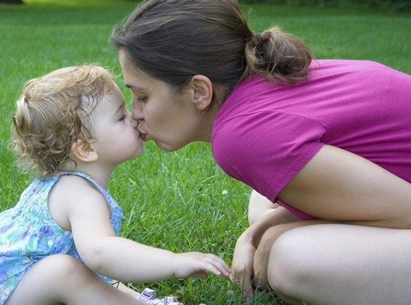 Mother kisses Little Daughter 2 year toddler girl on grass lawn
