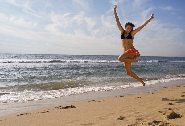 pretty young girl is jumping up in the air at the beach