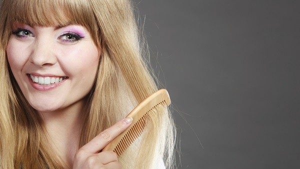 Fashion beauty and haircare concept. Closeup blonde woman refreshing her hairstyle girl combing hair with wooden comb gray background