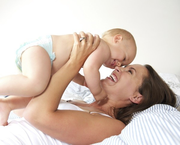 Close up portrait of a cheerful mother and cute baby playing