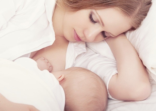 mother feeding breast her baby in the bed. sleeping together