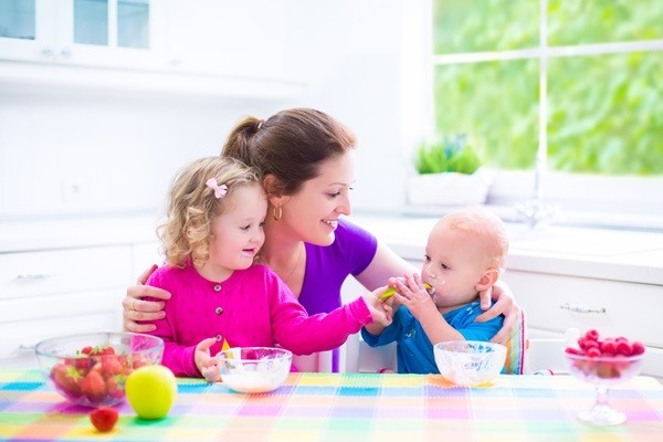 Happy young family, mother with two children, adorable toddler girl and funny baby boy having healthy breakfast eating fruit and dairy, sitting in a white sunny kitchen with window