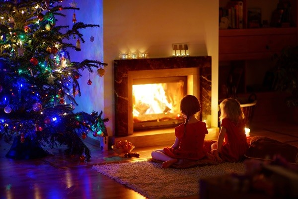 Happy little girls sitting by a fireplace in a cozy dark living room on Christmas eve